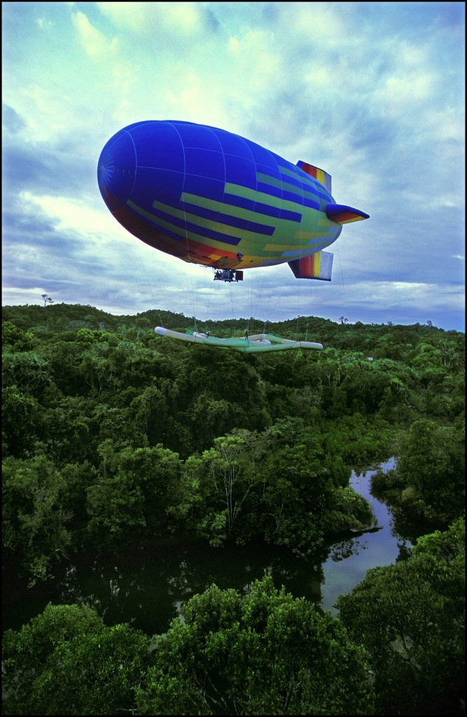 The dirigible flies the Pretzel, the Treetop Raft, toward the trees on which it will be laid.